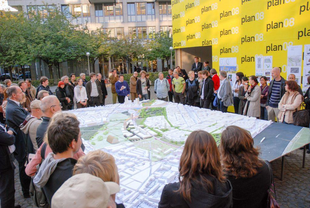 """Im Rahmen von """"plan 08 - Forum aktueller Architektur in Köln"""" war der hdak-Kubus bereits vor seiner Fertigstellung Veranstaltungsort. Am 26.09.2008 wurden hier anhand eines 25 m² großen Arbeitsmodells die Ergebnisse des Workshops """"Grüngürtel plus – BUGA 2021"""" vorgestellt und diskutiert."""